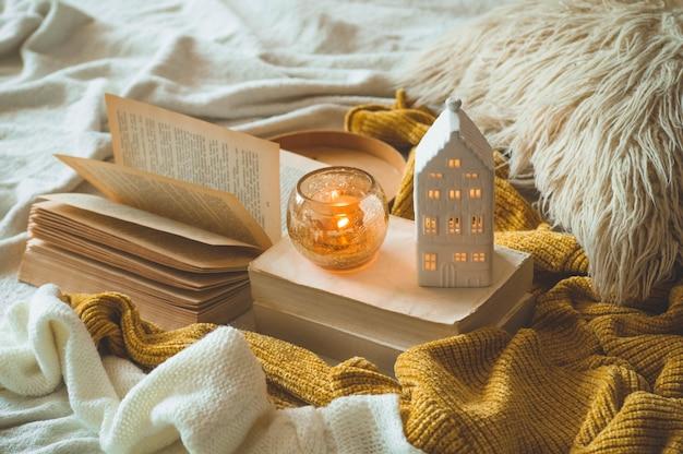 甘い家。リビングルームのインテリアの静物詳細。セーターとキャンドル、本の秋の装飾。読んで、休憩。居心地の良い秋や冬のコンセプトです。
