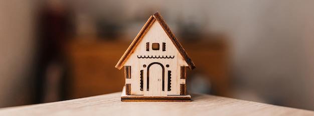 甘い家。ぼやけた背景とテーブル上の木造住宅
