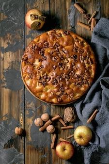 Сладкий домашний пирог с яблоками и грецкими орехами шарлотта на тарелке со свежими садовыми яблоками, корицей и орехами вокруг на фоне темной деревянной доски. осенняя домашняя выпечка. плоская планировка, копия пространства