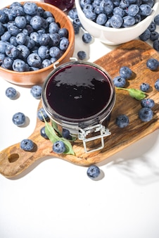 Sweet homemade blueberry jam in small glass jar on a white background, with fresh berries copy space