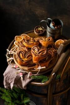 Сладкие домашние булочки с корицей в форме сердца на старом ретро-стуле. новогоднее настроение.