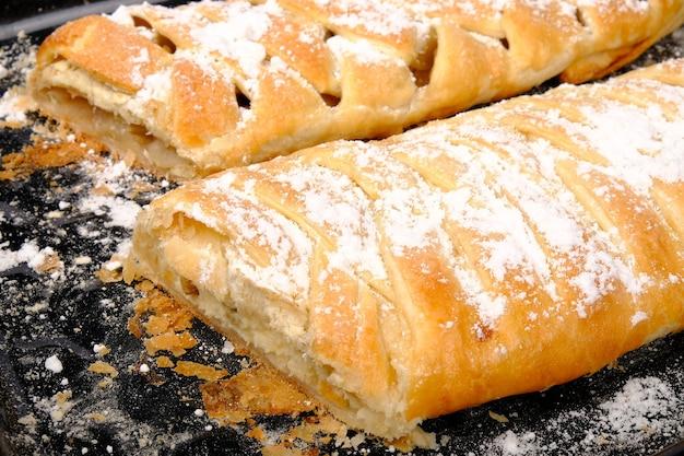 Сладкая домашняя свежая выпечка. пироги из слоеного теста со сладкой начинкой на крупном плане противня.