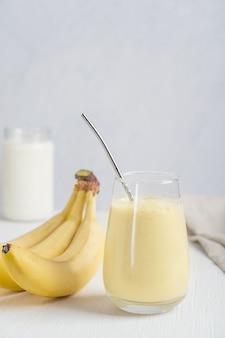 Сладкий домашний индийский напиток ласси из йогурта, смешанного со спелым бананом, подается в стакане на столе