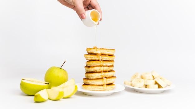 バナナ、リンゴ、蜂蜜またはメープルシロップの甘い自家製パンケーキ