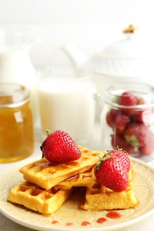 Sweet homemade waffles with fresh strawberries on plate, on light background