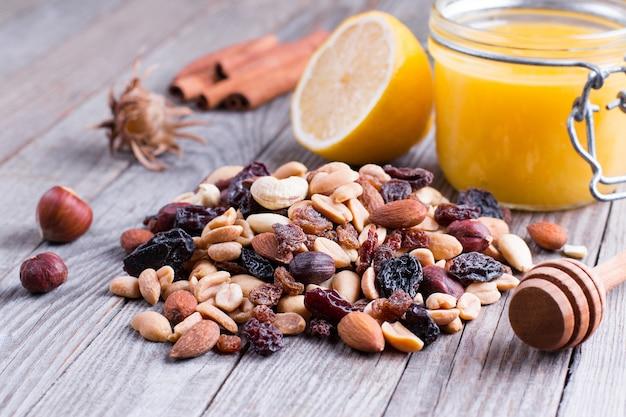 Сладкий мед и разные орехи на деревянном столе