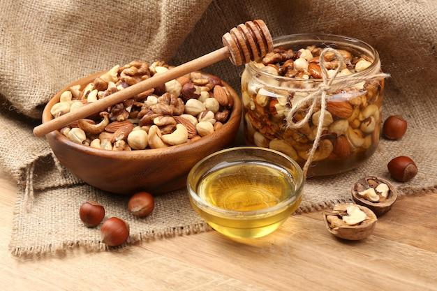 木製のテーブルに甘い蜂蜜とさまざまなナッツ
