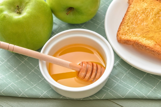 Sweet honey, apples and toasted bread on table