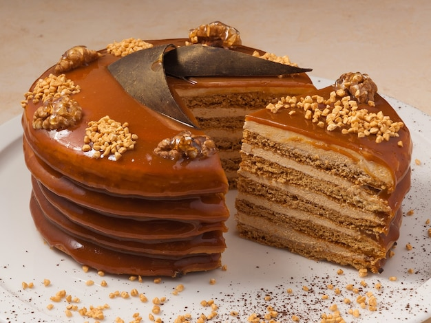 Sweet honey cake decorated with walnuts and caramel