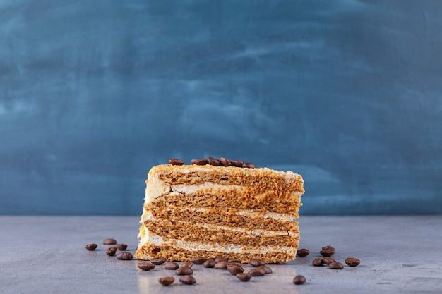 Sweet honey cake with coffee beans on marble background.