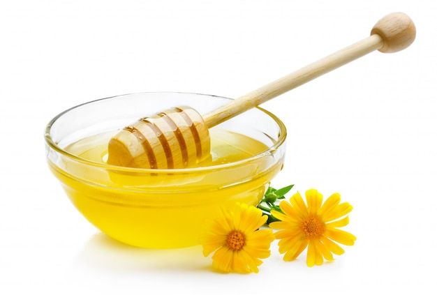 Sweet honey in glass bowl isolated with wooden dipper