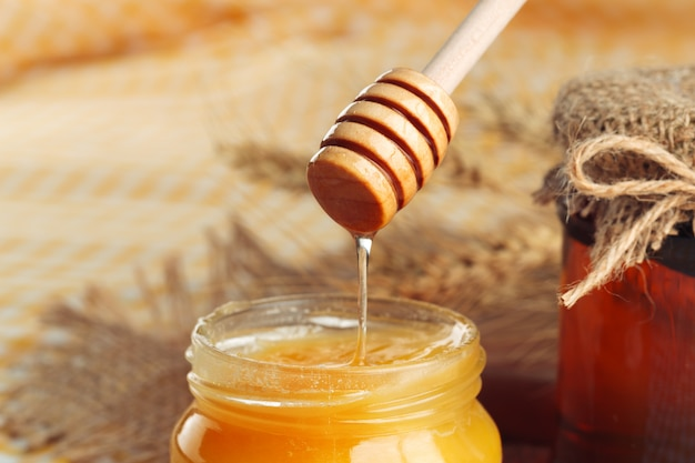 Sweet honey in glass jar on wooden background.