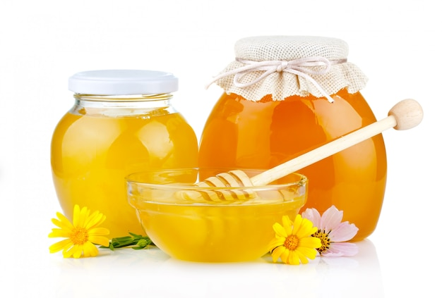 Sweet honey in glass jars with flowers and dipper isolated