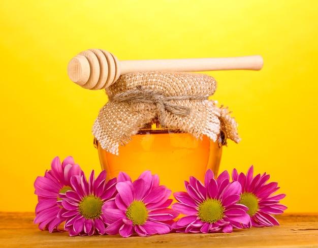 Сладкий мед в банке с капельницей на деревянном столе на желтом фоне