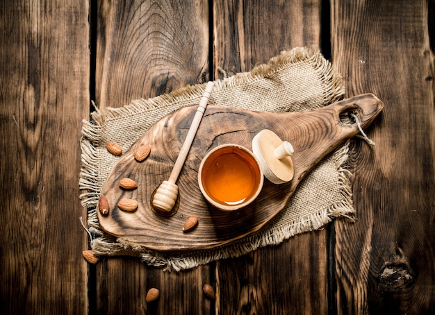 Сладкий мед в бочке на деревянной доске. на деревянном фоне.