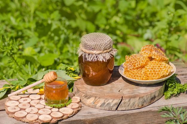 Сладкий мёд, кусочки расчесок и медовый ковш. мед капает из ковша. сельский или деревенский стиль