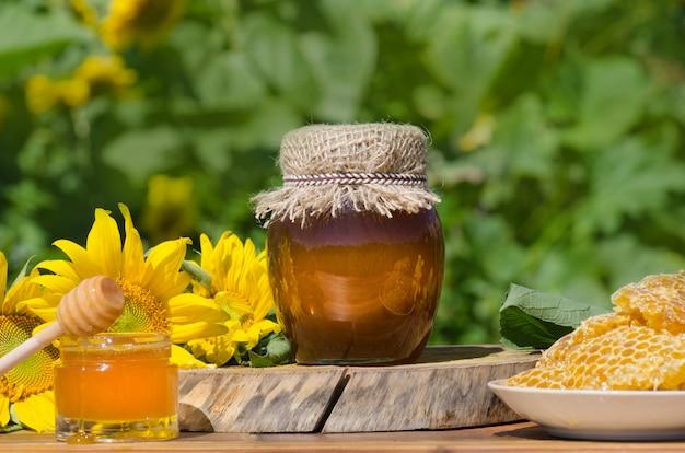 Сладкий мёд, кусочки расчесок и медовый ковш. мед капает из ковша