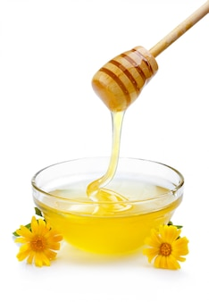 Sweet honey pouring from wooden dipper in glass bowl isolated