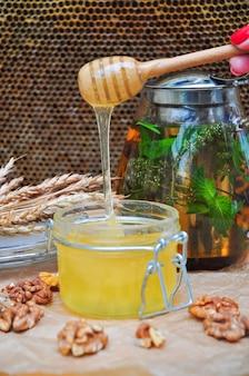 Сладкий мед с заварником травяного чая, украшенным грецкими орехами