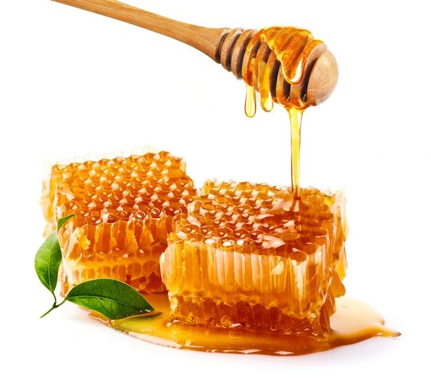 Сладкий сотовый и деревянный мед капает изолированные на белой поверхности. медовый ковш