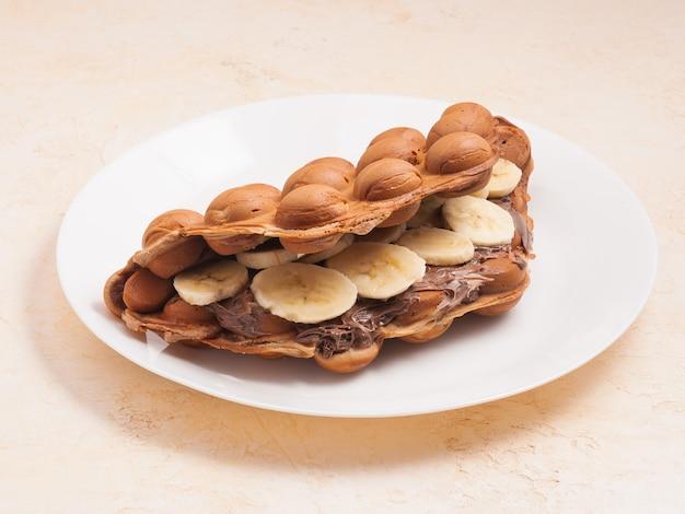 Сладкие гонконгские вафли с бананом и шоколадной пастой на белой тарелке