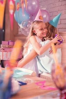 甘い抱擁。素敵なプレゼントを持って母親を抱きしめながら、幸せそうに笑って感謝を感じる元気な誕生日の女の子
