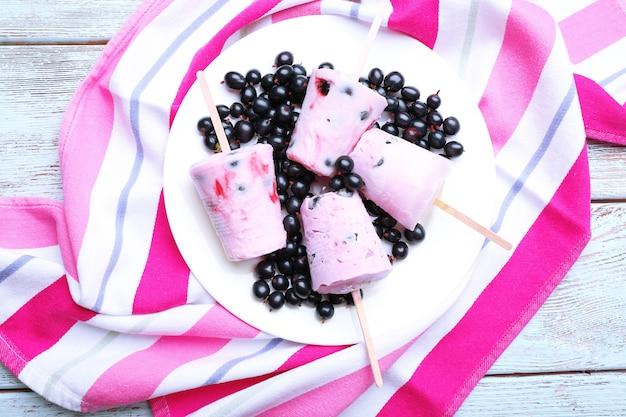 Сладкое мороженое с черной смородиной в белой тарелке на полосатой салфетке, крупным планом