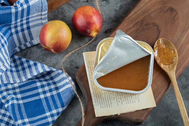 木の板に桃と木のスプーンで甘いジャム