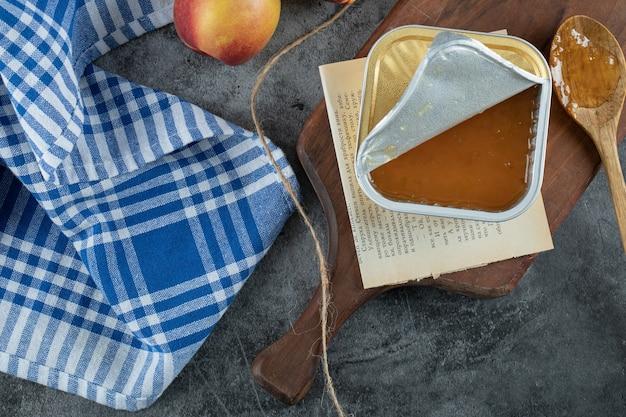 Marmellata dolce con pesche e cucchiaio di legno su tavola di legno