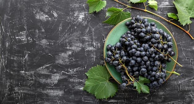 Sweet juicy black grapes food on dark concrete background flat lay with copy space. black grapes in green vintage plate with vine plant on dark table top view. long web banner.