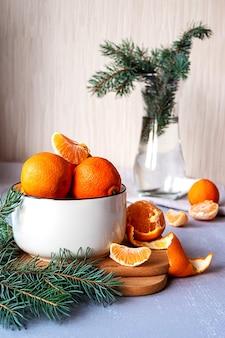 Сладкие сочные мандарины в белой миске с еловыми ветками в вазе на столе