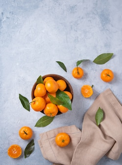 Sweet and juicy tangerines in a wooden bowl and with linen napkin