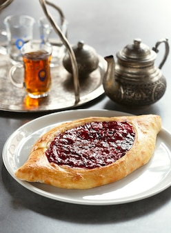 Sweet khachapuri with cream cheese and raspberry jam on a plate