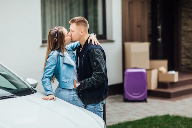 Dolce bacio. la coppia felice è in piedi vicino alla nuova auto e alla casa con scatole di cartone.