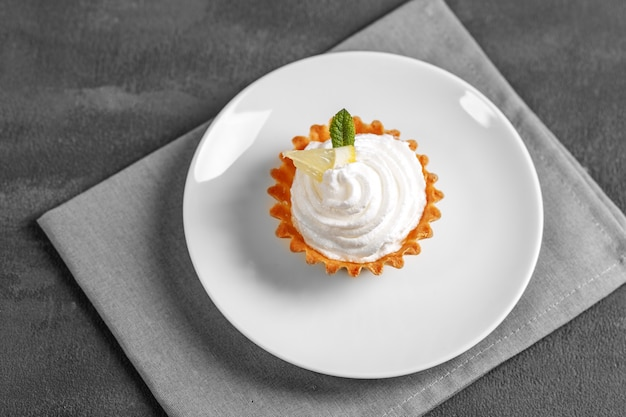 Sweet lemon cake with cream on the plate.