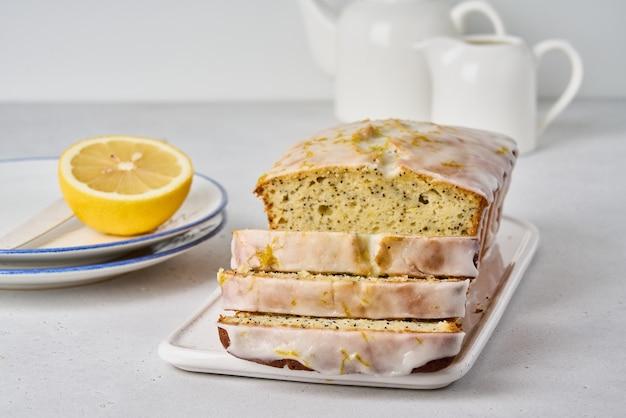 ケシの実の白いアイシングと柑橘類の皮の国内デザートの甘いレモンパティスリー