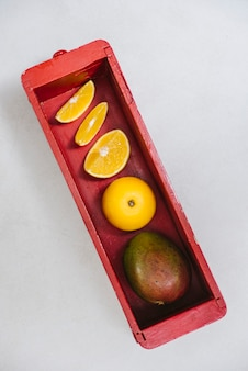 Sweet lime and mango in red wooden container