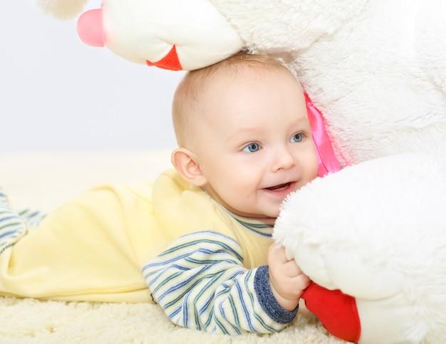 おもちゃで笑って、甘い小さな赤ちゃんの顔