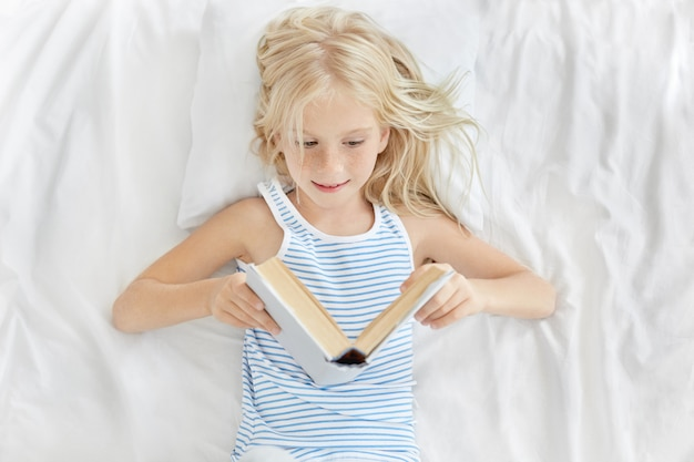 Sweet little blonde 7-year old girl of european appearance resting in white bed, looking in open book with interest while reading fairytal