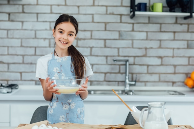 Sweet little cute girl is learning how to make a cake, in the home kitchen, family concept