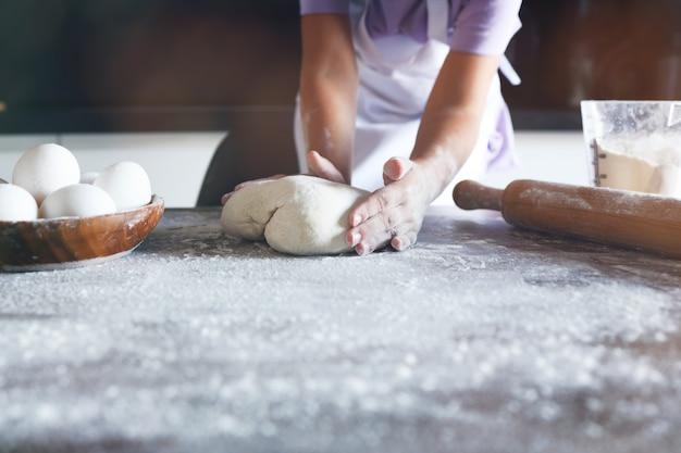 작고 귀여운 소녀가 가정 주방에서 케이크 만드는 법을 배우고 있습니다. 가족 개념, 빈티지 색조입니다. 평면도
