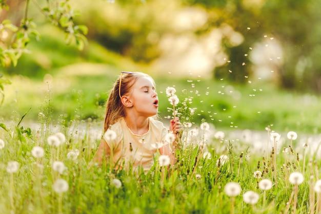 Sweet little girl blowing dandelion