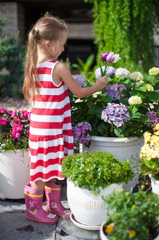 Sweet little girl holding a bouquet of tulips in the yard