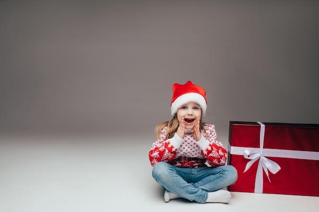 サンタの帽子とセーターを着たかわいい女の子がクリスマスプレゼントの隣に座って、口に手を当ててカメラに何かを発表しました。スペースをコピーします。
