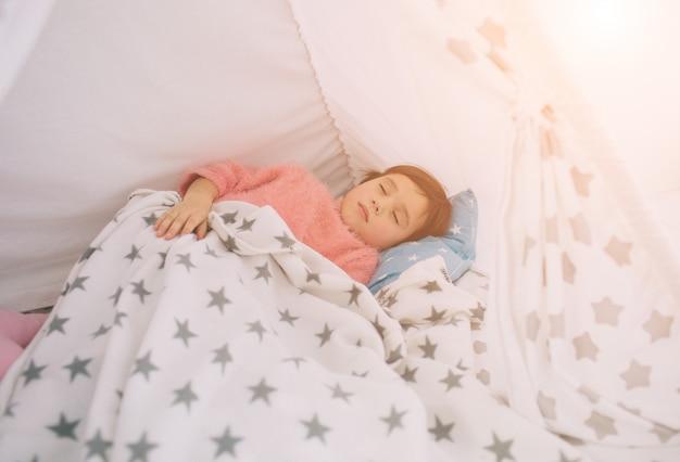 かわいい女の子が寝ています。赤ちゃんは家で寝ています。