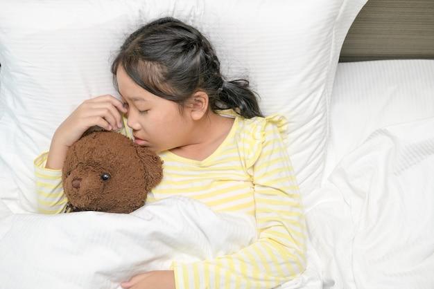 달콤한 작은 소녀는 집, 달콤한 꿈과 휴식 개념에서 그녀의 침대에서 테디 베어와 함께 자고있다