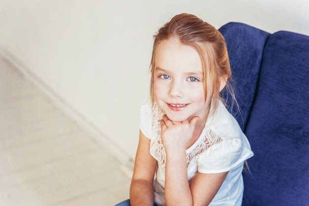 Sweet little girl in jeans and white t-shirt sitting on blue chair relaxing at home