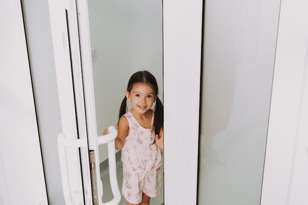 Sweet little girl opening door pediatric clinic.