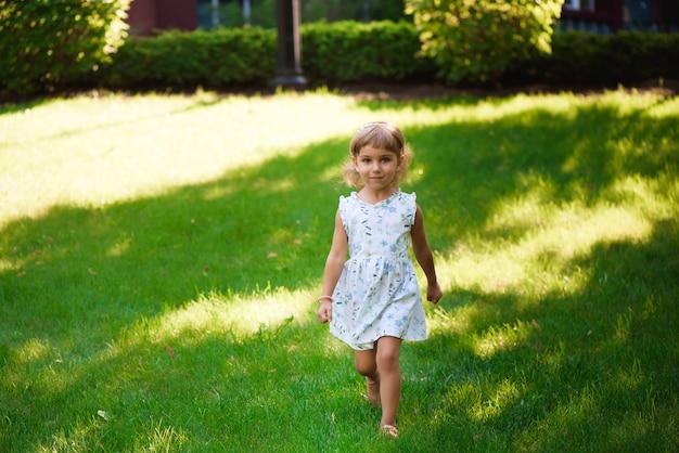 바람에 곱슬 머리를 가진 야외에서 달콤한 작은 소녀.