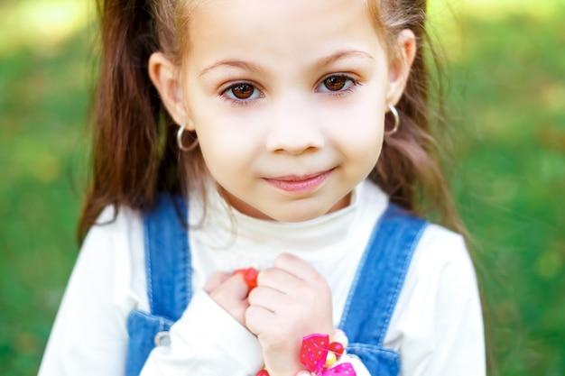 Милая маленькая девочка на открытом воздухе с вьющимися волосами в два длинных хвоста, крупным планом